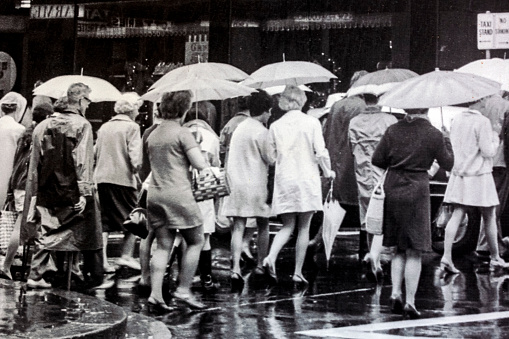 Sydney, Australia - 1969: Detail of black and white photo from 1969 Sydney Market Street with group of people with umbrellas in rainy day crossing street in the city