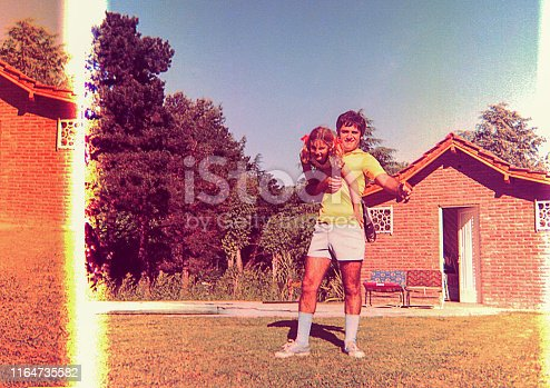 Vintage and damaged photo of a girl and her father playing outdoors