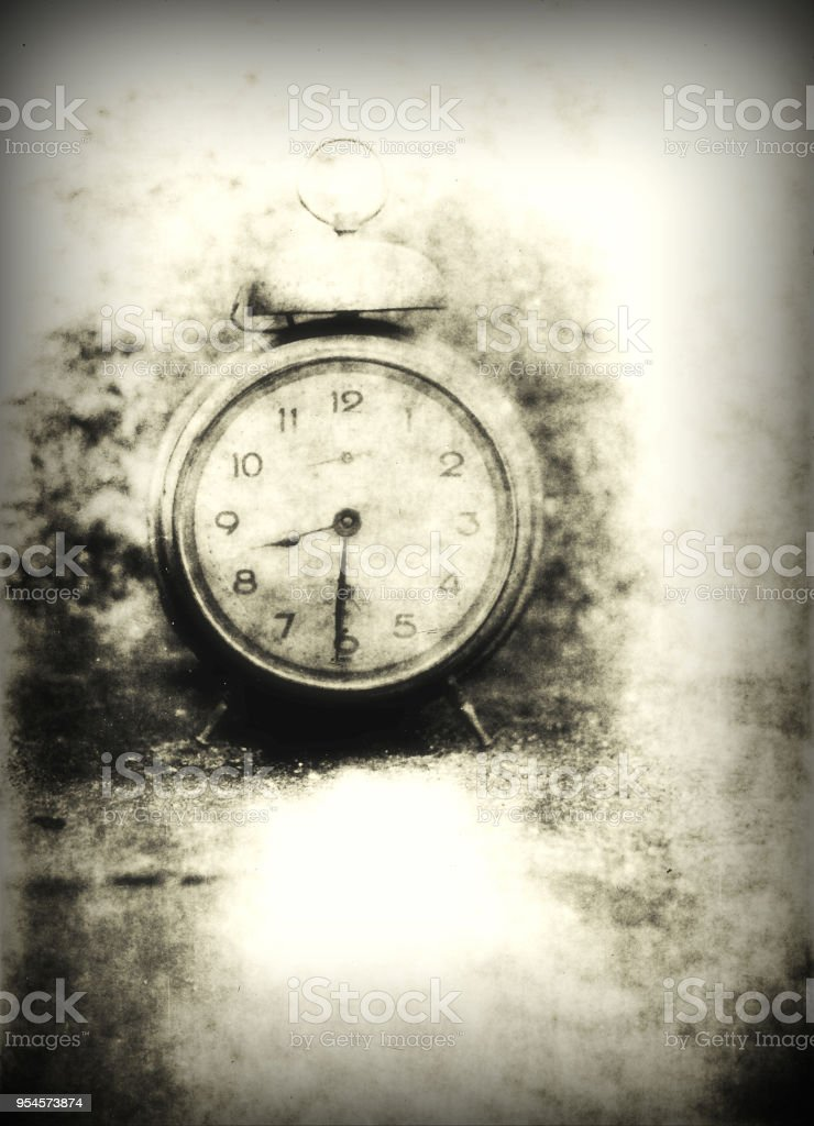 Old photo of the alarm clock - grained, scratched, overexposure and underexposure stock photo
