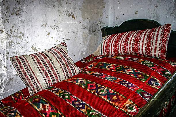 altes photo mit rumänische traditionelle home interior - bauernhaus bett stock-fotos und bilder