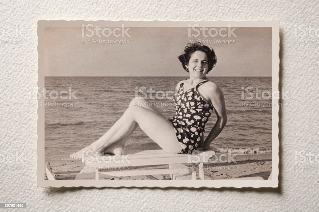 Old photograph of a smiling girl at sea. Photograph of the 50s. stock photo