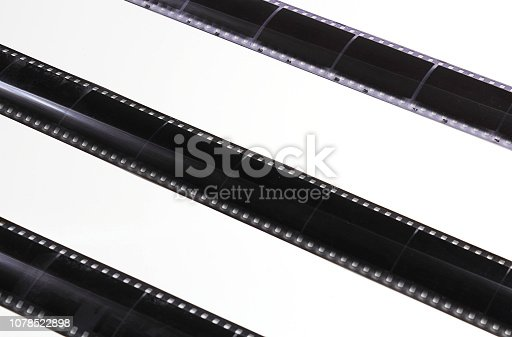 Old photographic film on a light background, strip. The concept of history, home archives, memorable dates. Selective focus, close-up.