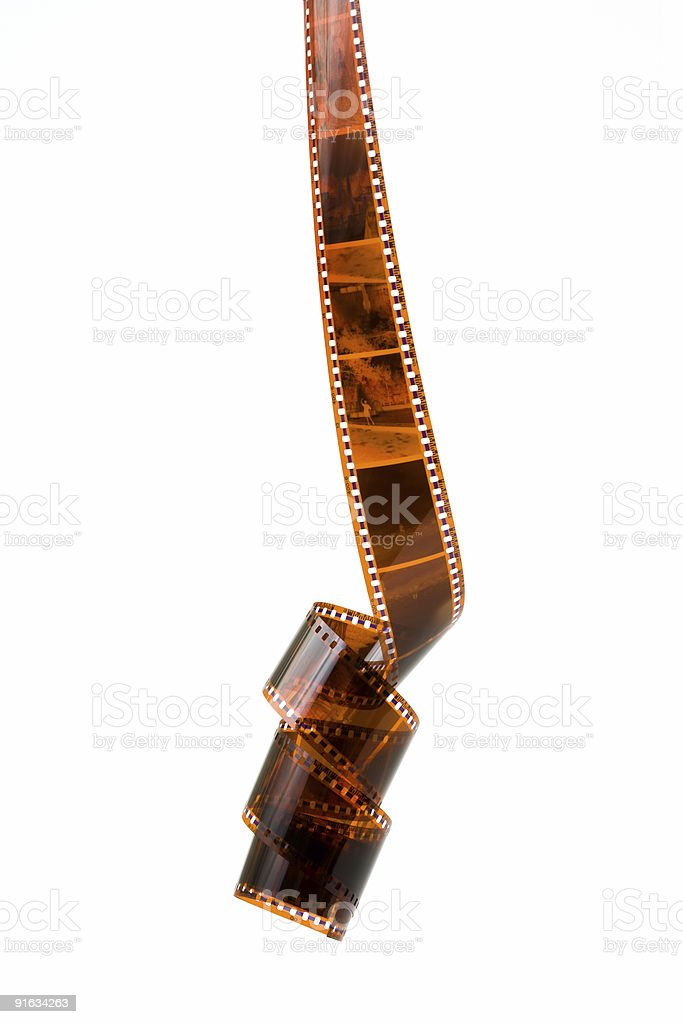 Old photographic film unraveled and isolated on background royalty-free stock photo