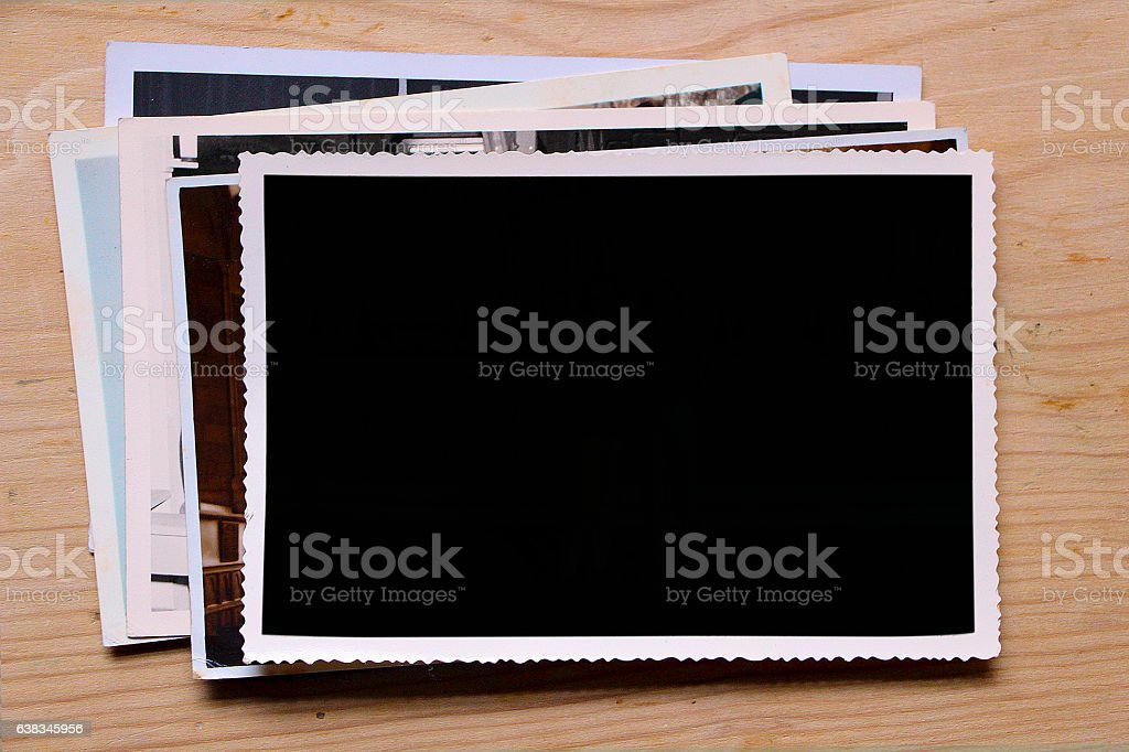 Old photographs on wood table (with clipping path) stock photo