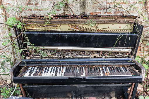 old piano with concrete wall and leaf