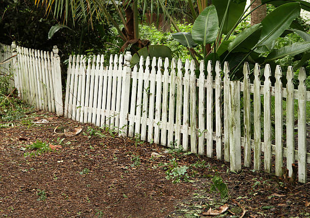 Old picket fence in need of repair and painting stock photo