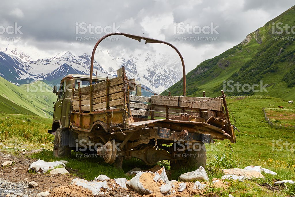 old pickup truck on a mountain road stock photo