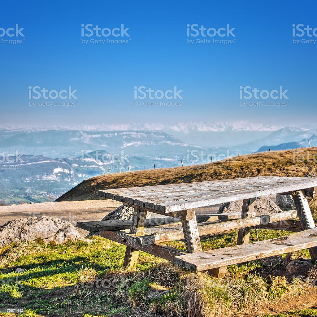 Square composition photography of old picnic wooden table with bench...