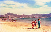 vintage saturated image of a mother and her children at the beach in Acapulco.