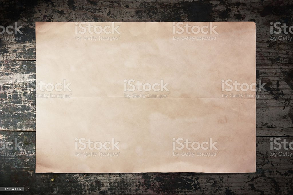 Old piece of paper on a wooden wall royalty-free stock photo