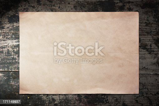 istock Old piece of paper on a wooden wall 171149937
