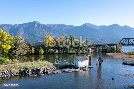 Autumn landscape with an old abandoned rotten wooden pier in the bay of the Columbia River with yellow autumn trees on the shore and railway bridge over the canal in Columbia River Gorge area