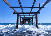View of the surf waves from under a rusty metal pier. Seascape on a sunny day.