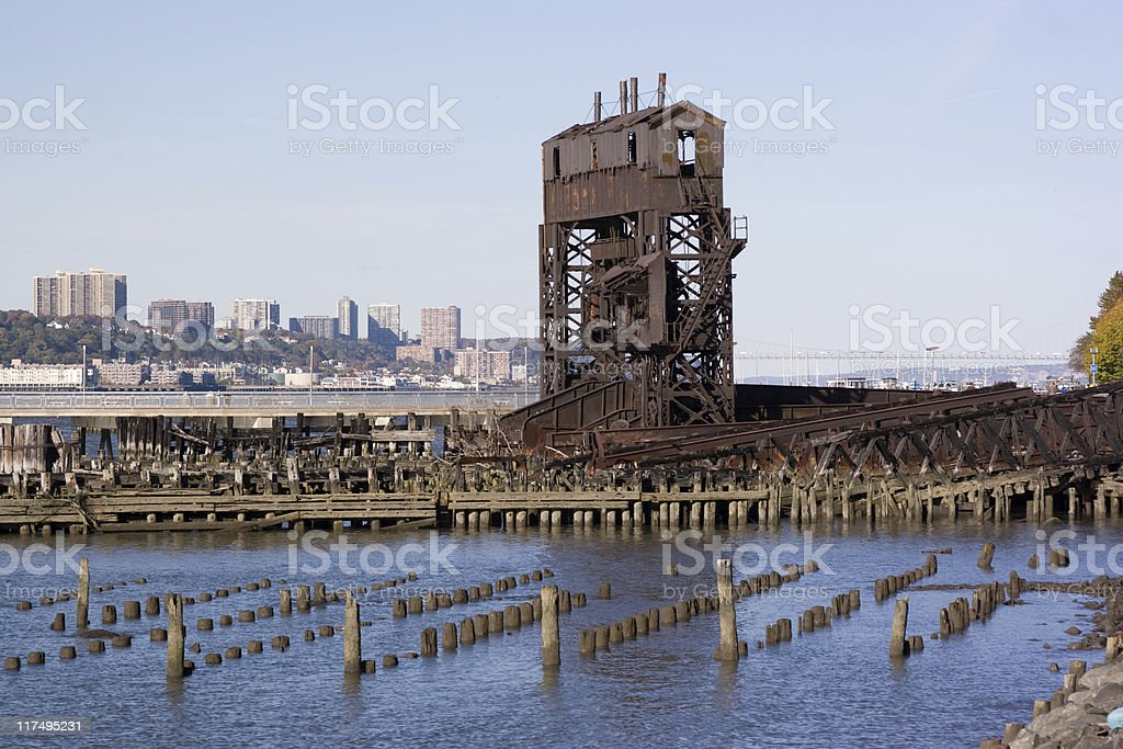 old pier stumps in front of an old mining site stock photo