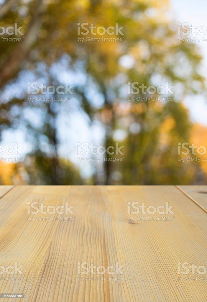 Ancienne table de pique-nique pin, texture de grain de bois naturel. Idéal pour positionner les produits sur et placent au premier plan de n'importe quelle image.  Mise au point sélective. Très faible profondeur de champ pour le fond doux. Forêt d'automne en arrière-plan. photo libre de droits