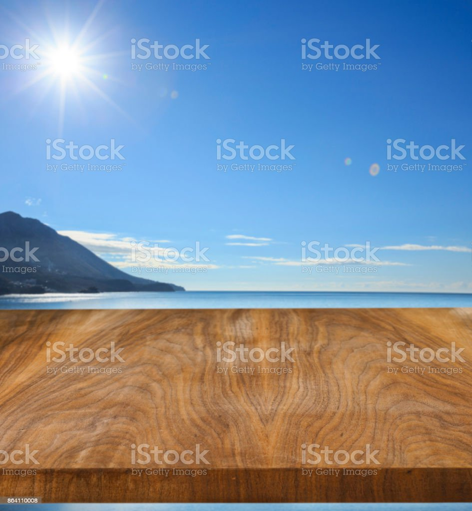 Old pine picnic table, natural  woodgrain texture. Ideal to position products on and place in the foreground of any image.  Selective focus. Very shallow depth of field for soft background. Sea in the background. royalty-free stock photo