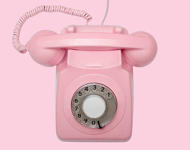 Old pink telephone on pink background with path stock photo