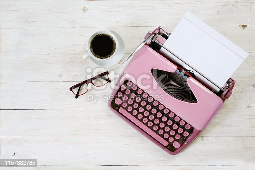 istock Old pink typewriter from the 1950s with blank paper, coffee and glasses on white painted rustic wood, copy space, high angle view from above 1157332785