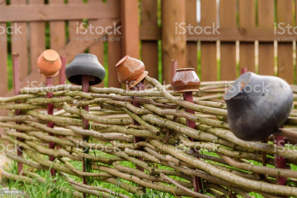 Old pitchers on a wooden fence. Decorative elements of landscape design under the antiquity. zbiór zdjęć royalty-free