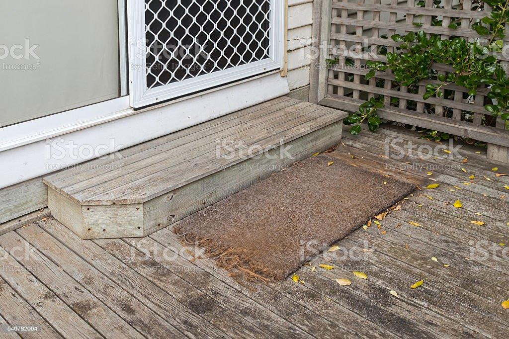 Old plain coir doormat placing in front of the doorstep stock photo