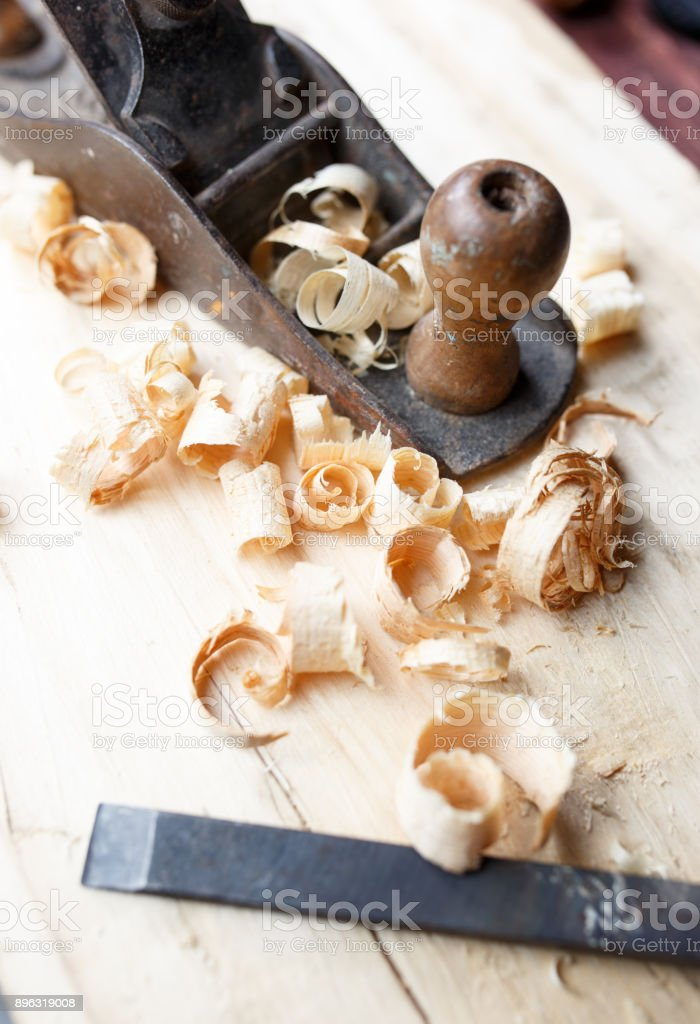 Old plane on wooden board, carpentry tools with wood shavings stock photo