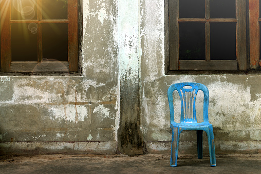 Old plastic chair near old cement wall.
