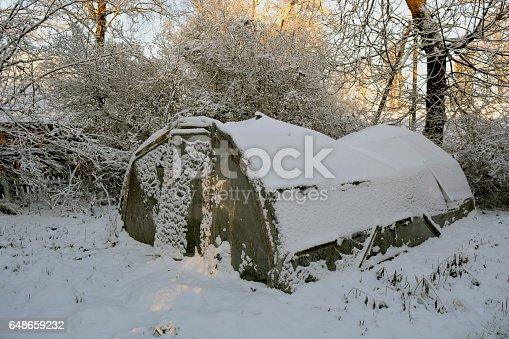 old broken plastic greenhouse in derelict farm and winter snow