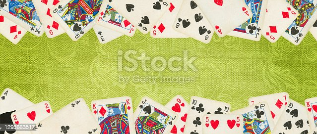 Old Playing cards on green playing table (clipping path included)