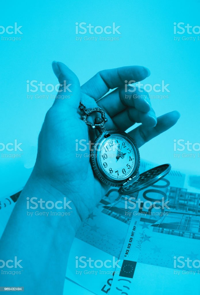 Old pocket watch hold in a hand, 500 euro banknotes money on the background. Time and business concept. royalty-free stock photo