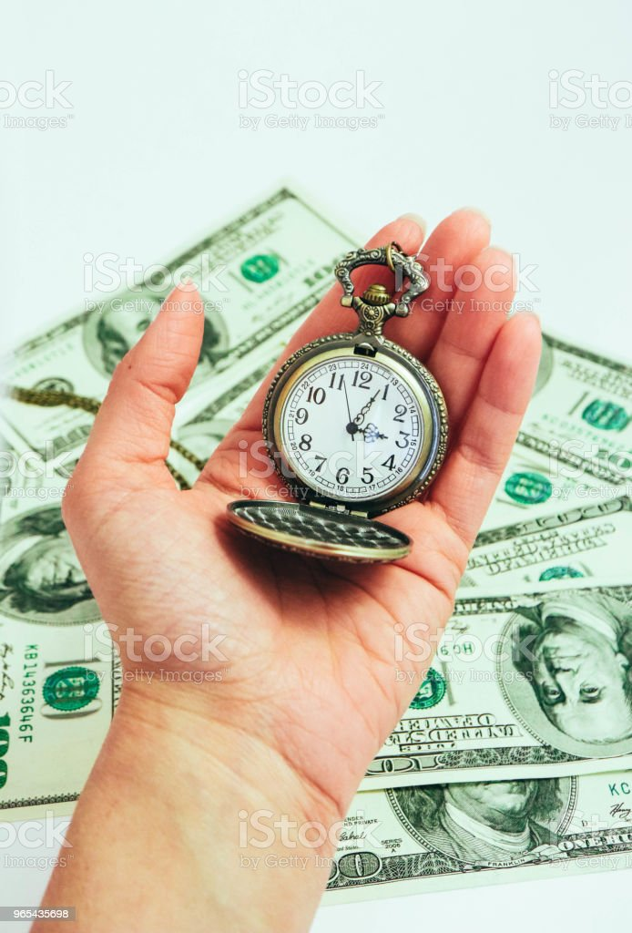 Old pocket watch hold in a hand, American dollar banknotes money on the background. Time and business concept. royalty-free stock photo