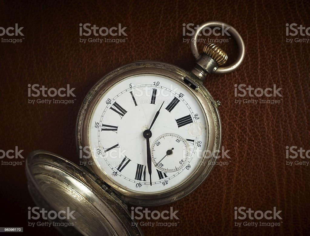 Old pocket watch on the natural brown leather background. royalty-free stock photo