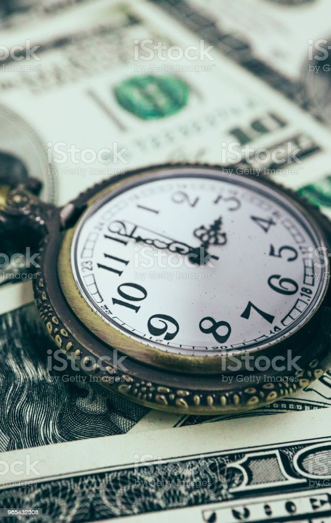 Old pocket watch with American 100 dollar banknotes money with Franklin president portraiture, macro view. Time and business concept. royalty-free stock photo