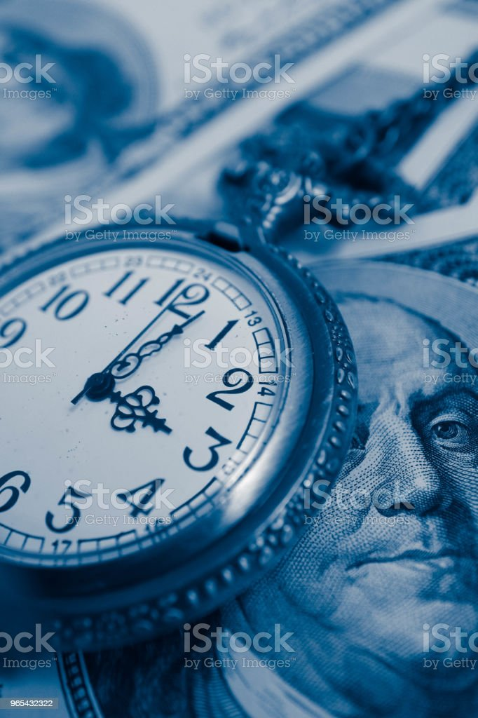 Old pocket watch with American 100 dollar banknotes money with Franklin president portraiture, macro view. Time and business concept. zbiór zdjęć royalty-free