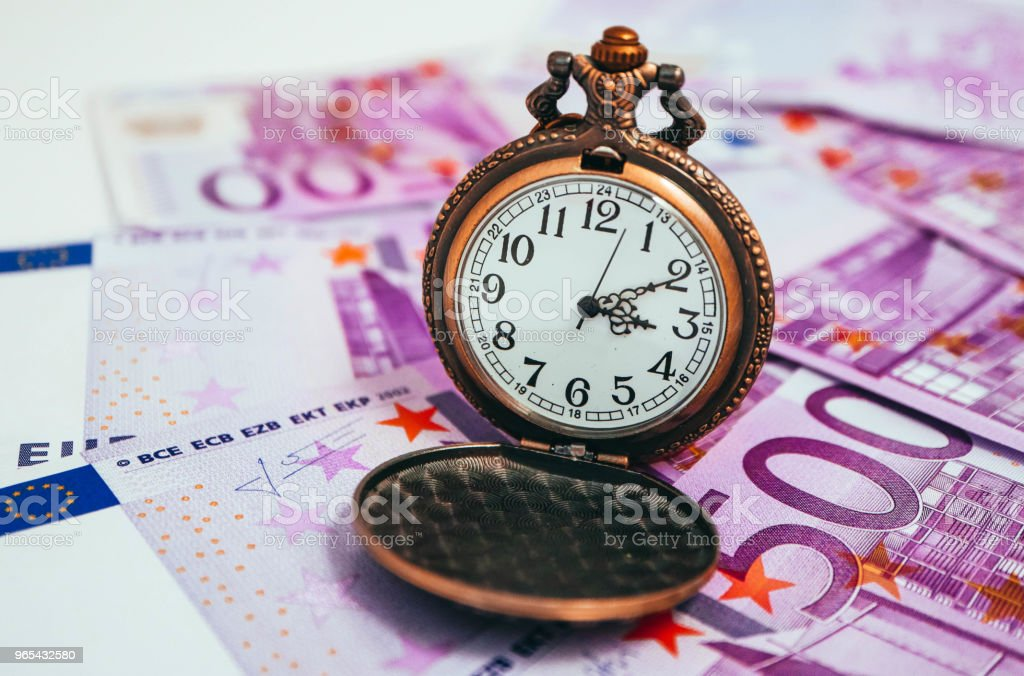 Old pocket watch with euro banknotes money, macro view. Time and business concept. royalty-free stock photo
