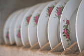 old porcelain plates with floral decoration in wooden shelf