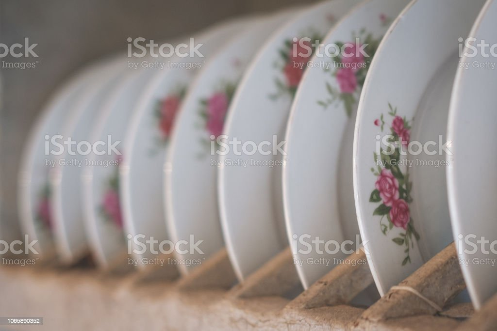 old porcelain plates with floral decoration in wooden shelf - stock photo