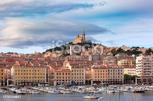 The old Vieux Port and Basilica Notre Dame de la Garde in the historical city center of Marseilles on sunny day, France