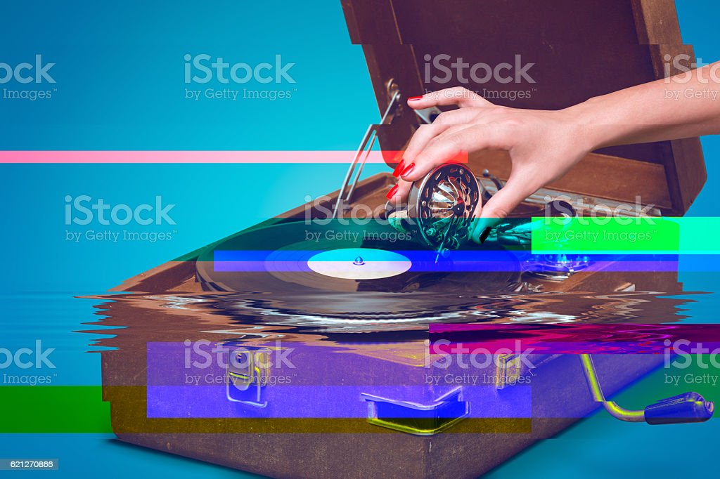 Old portable gramophone with female hand and glitch effect stock photo