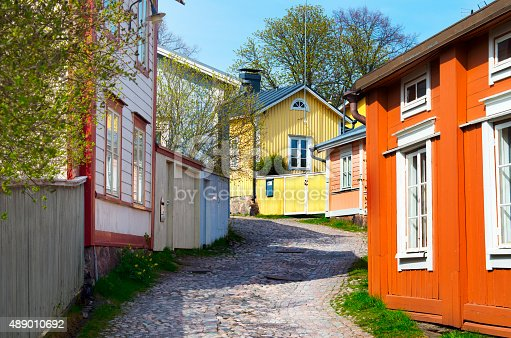 Street view in the old part of the city of Porvoo, Finland,  on a sunny spring day. Wooden empire-style homes painted in yellow, orange and pink surround the cobblestone-paved street.