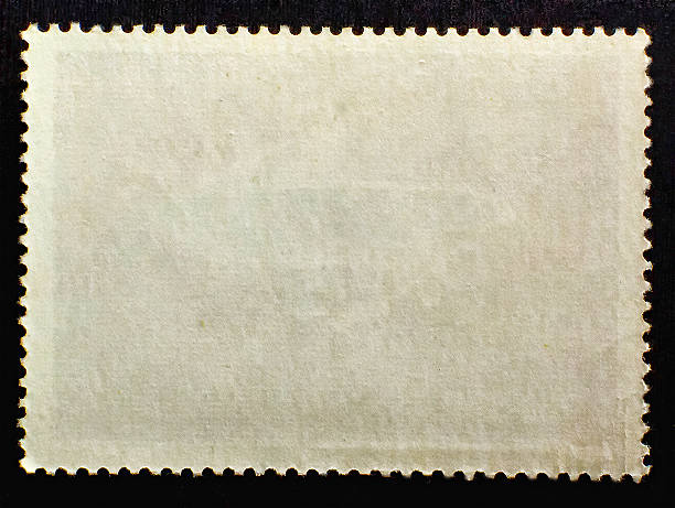 old posted stamp reverse  side isolated on black background - stamp 뉴스 사진 이미지