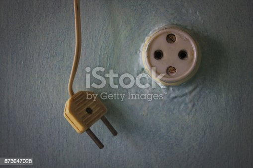 Vintage plug on the wire hangs next to the old socket