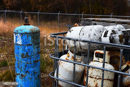 An image of used and damaged propane cylinders at a recycling tacitly.