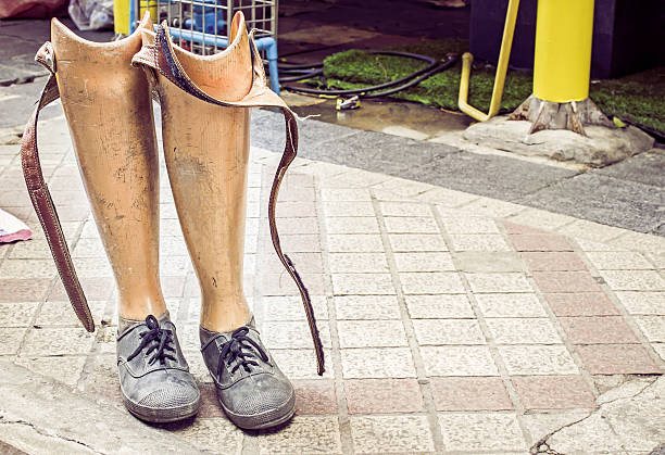 Old prosthetic legs set on a cement floor stock photo
