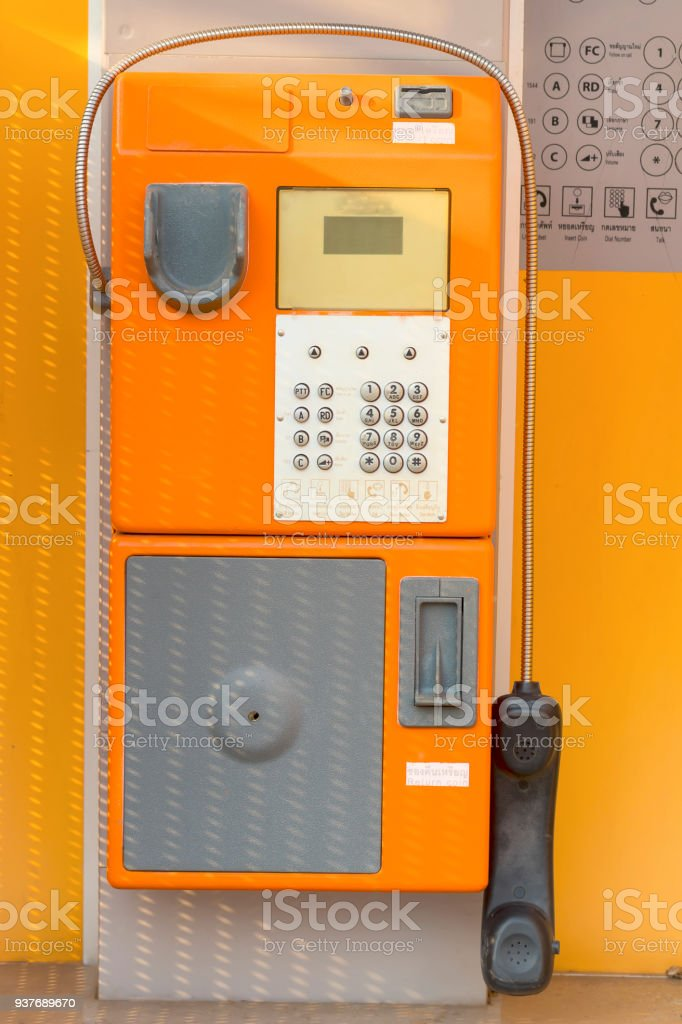 old public phone booth orange color for coins stock photo