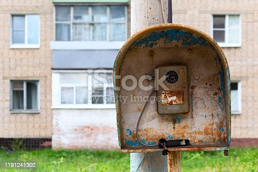 istock Old public russian wired urban telephone post - useless abandoned and broken. 1191241302