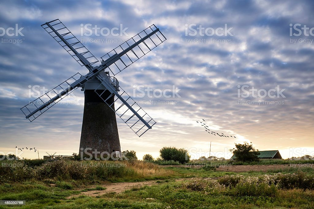 Old pump windmill in English countryside landscape early morning stock photo