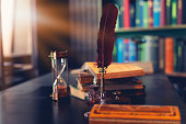 istock Old quill pen, books and vintage inkwell on wooden desk in the old office against the background of the bookcase. Conceptual background on history, education, literature topics. 1273452357