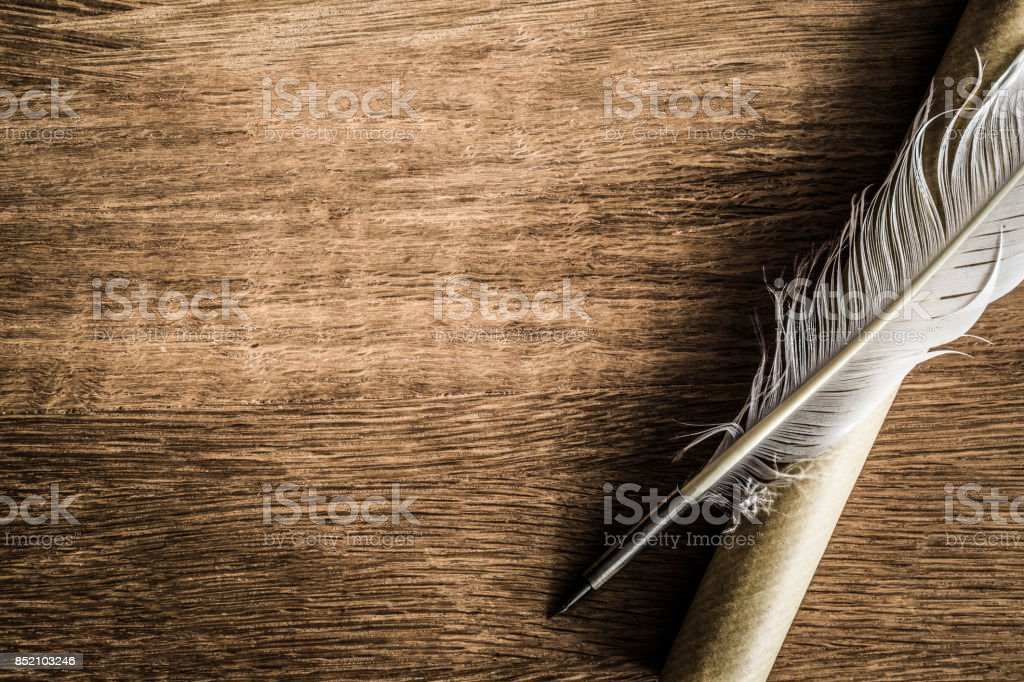 Old quill pen with old paper scroll on the dark wooden table. Letter writing. Historical atmosphere. stock photo