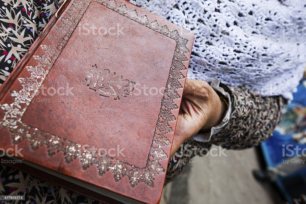 Old Quran in the lap of a lady royalty-free stock photo