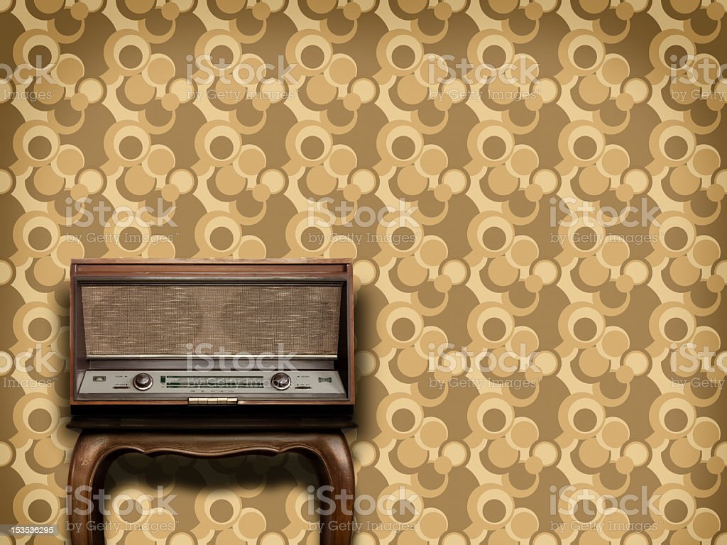 Old radio equipment on wooden table and vintage wallpaper stock photo